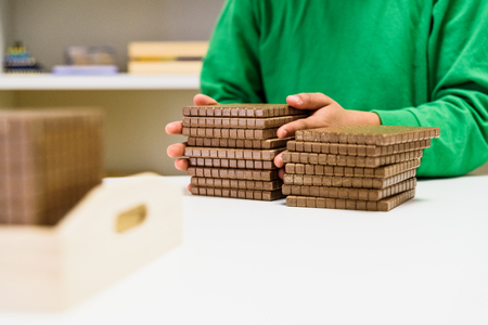 Child placing some blocks to count numbers is his house, concept of homeschooling.