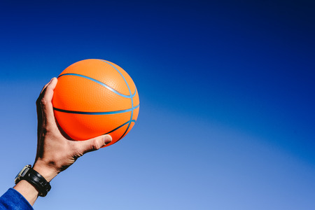 Hand holding an orange basketball ball on blue sky background, invitation to play, copy space free area.