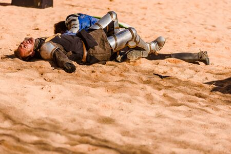 Valencia, Spain - January 27, 2019: Two actors disguised as medieval knights lying on the ground defeated after a sword battle in a performance during a medieval spring festival. Éditoriale