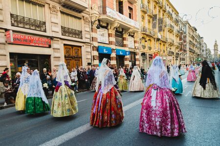 Valencia, Spain - March 17, 2019: Fallera Commission parading down Calle de la Paz, seen from behind, during the Fallas offering. 新聞圖片