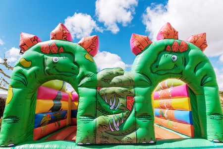 Bouncy castle in the shape of dinosaurs in a childrens playground outdoors.
