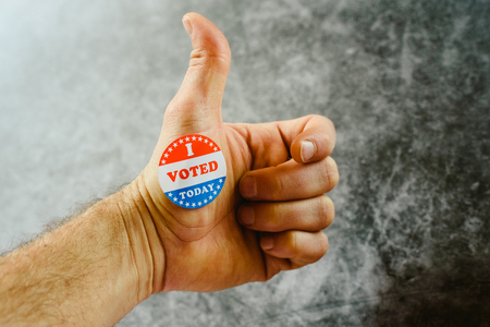 Man's hand teaching that he has voted today in the American elections with a sticker.