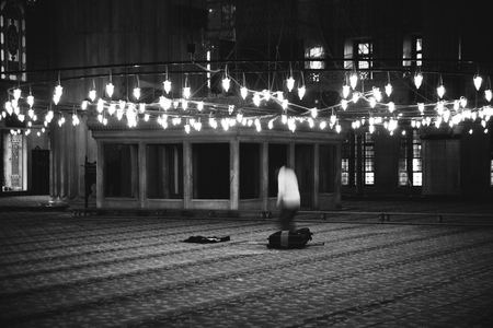 Muslim believer praying inside a mosque, black and white photo, grain film added. Editorial