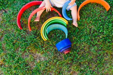 6 month old baby using to play a wooden rainbow puzzle, improving his skills, view from above. Imagens