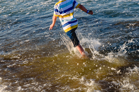 Young child having fun getting wet and splashing on the shore of the beach running between the waves. Banco de Imagens - 124726869