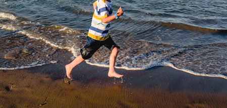 Young child having fun getting wet and splashing on the shore of the beach running between the waves.