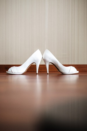 Vertical image of a white womens shoes with high heels.