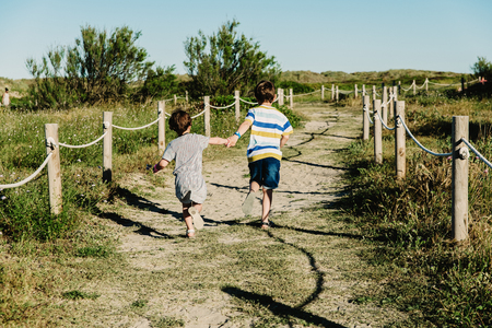 Two siblings running hand in hand in a field happy and free.