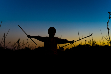 Silhouette of boy playing at dusk in summer with some sticks as weapons. 版權商用圖片