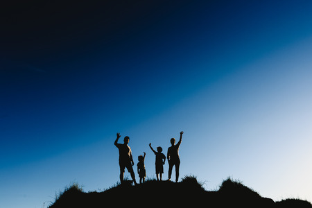 Silhouette of a happy family on top of a hill waving at sunset. Banco de Imagens