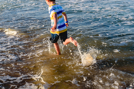 In summer children have to exercise outdoors and go out to sea to run alongside the waves. Banco de Imagens - 124726938