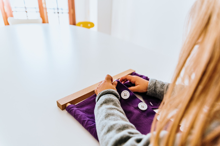 Hand of a student handling montessori material inside a classroom.