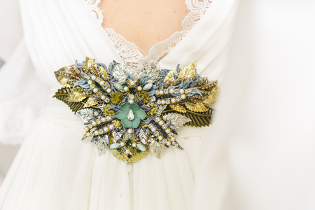 Flower shaped brooch made with small gemstones for a wedding dress. Фото со стока