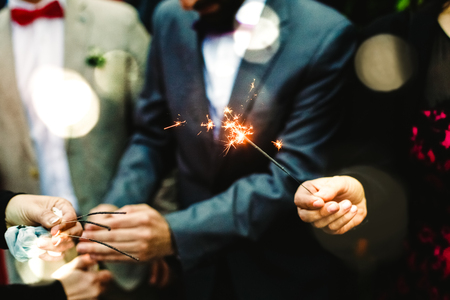 Elegant men holding a flare lit during a party Фото со стока