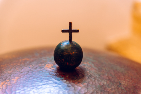 Christian cross on a small metal ball, negative space.