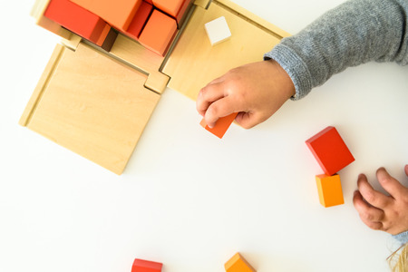 Childs hands using an educational toy for their cognitive development. Imagens