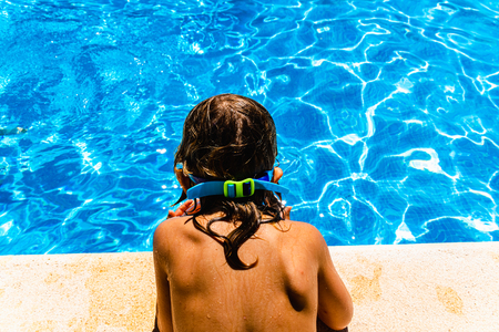 Child with a tanned back to the sun, observing the fresh and transparent water of a pool.