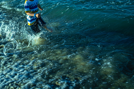 Child running on the sand of the beach splashing with waves in summer. 版權商用圖片