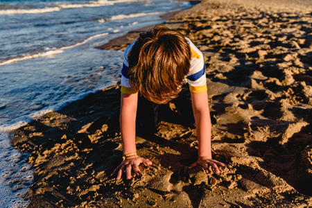 Child playing in the sand on the beach, kneeling hiding his face.