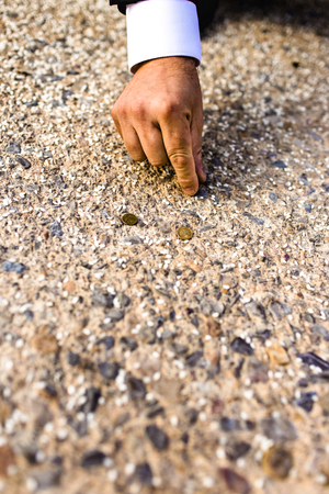 Businessman hand picking up some coins that have fallen to the ground, concept of opportunities.