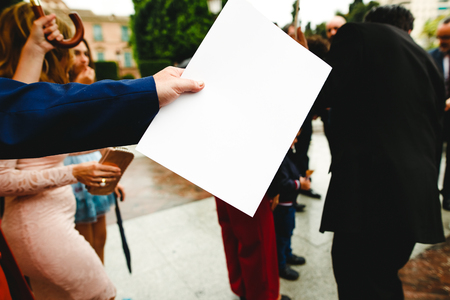 Businessman hand handing a blank paper with important information, copy space for text.