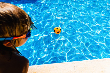 Boy observing a ball moving away from him in a pool in summer, concept of achievable goals in childhood.