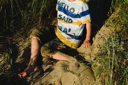 Boy enjoying the summer playing to dirty his clothes with the sand on the beach.