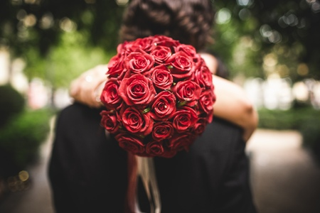 Bouquet of red roses held by a woman while hugging her lover.