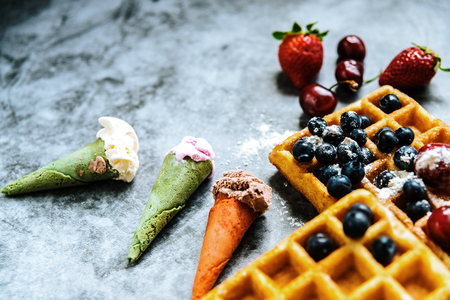 Background of foods refreshing ice cream in cones with red fruits and waffles, with negative space for summer design.