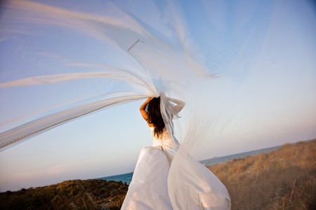 Newly-married bride with wedding dress on top of a hill letting her veil flutter in the wind, romantic image. Фото со стока