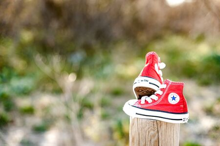 Valencia, Spain - March 3, 2019: Two red baby shoes from the Converse brand.