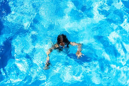 Girl dived and swimming in her private pool in the sun during her summer vacation.