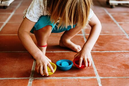 Child picking colorful wooden bowls from the floor, educational summer games.