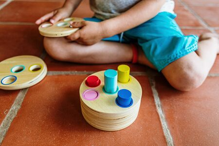 Child having fun with an educational wooden game, to fit cylinders into holes, improving spatial visual skills and their hands.