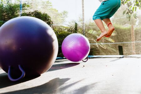 Boy enjoying his summer vacation jumping on a trampoline at dusk, with a couple of fitness balls.