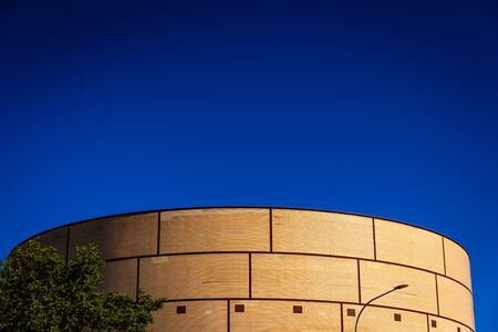 Background of intense blue sky in an industrial area with a brick construction with round shapes.