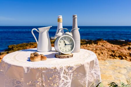 Antique alarm clock next to white decoration bottles, on a round table overlooking the sea and rocks, blue sky background and copy space. Фото со стока