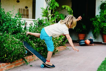 5 year old boy practicing skate in his backyard, stumbling and falling to the ground. Imagens