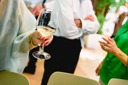 Older woman holding a glass of white wine at her retirement party. 写真素材 - 124727393