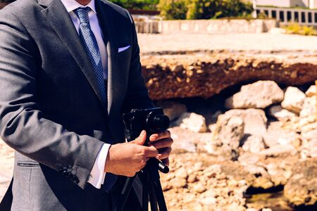 Man in a suit using a compact photo camera on a tripod to take a self-portrait to use as a profile in his business and social networks. Reklamní fotografie