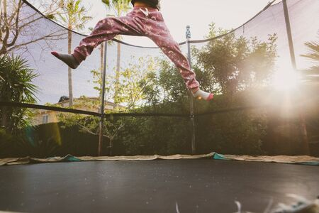 Little girl enjoying her vacation jumping on the trampoline doing acrobatic exercise outdoors.
