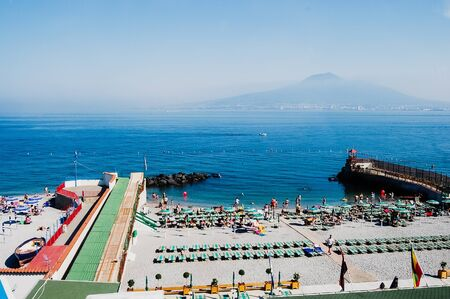 Sorrento, Italy - June 5, 2019: A beach with sunbathers in Sorrento, with background of unfocused view of Vesuvius volcano.