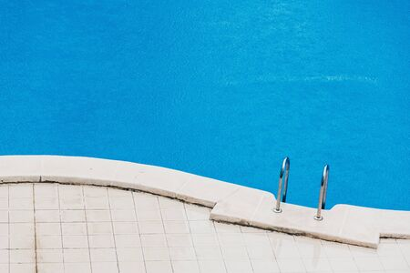 Summer storm, a fine rain falls on the blue water of a swimming pool in a hotel. Фото со стока
