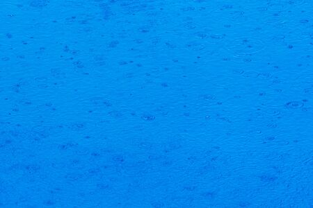 Image to use as background of rain falling on the water of a lake of transparent blue waters during a summer storm.