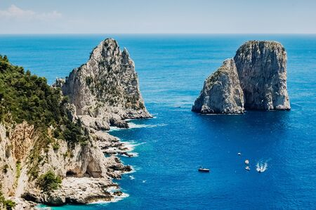 Natural rock arches and cliffs on the coast Sorrento and Capri, Italian islands with crystal clear waters where tourist boats crowd to photograph them in summer. Stock Photo