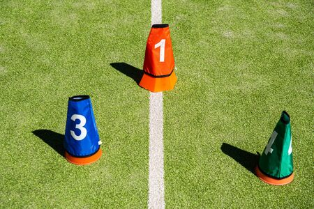 Background of sports cones for training on an artificial grass court.