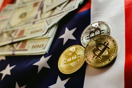 Bitcoins and 100 dollar bills with american flag background.