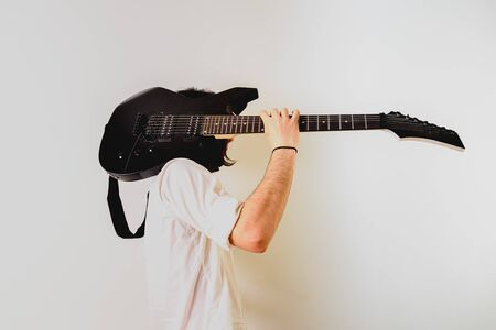 Guitarist posing with his electric guitar, white background.