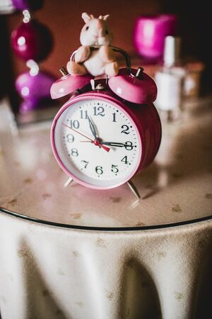 Vertical photo of a childrens pink alarm clock on a bedside table. 写真素材