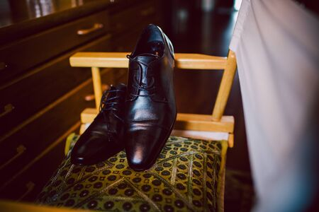 Black mens shoes, elegant and leather, resting on a chair on the bottom of a dark house.